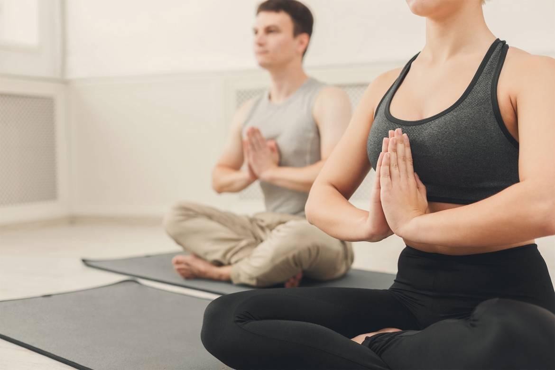 young-couple-practicing-yoga-sitting-in-padmasana-PAHA4NQ.jpg